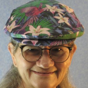 Ivy Flat Cap in Lily And Parrot With Mums at Dusk - model